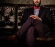 Old-fashioned bearded man sitting in comfortable leather sofa isolated on  gray. Stock Photos