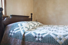 Old fashioned bed with quilt and oil lamp Stock Photo