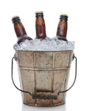Old Fashioned Beer Bucket Closeup. Closeup of an old fashioned beer bucket with three brown bottles of cold beer. Isolated on white with reflection Royalty Free Stock Image