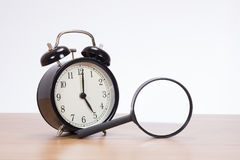 Old-fashioned bell alarm clock and magnifier Stock Photos