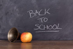 Old fashioned bell and apple against a blackboard Stock Image