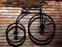 Old-fashioned  bicycle on a brick wall. Minimalism, room interior, decor, design. Old-fashioned  bicycle on a brick wall stock photos