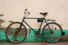 Old fashioned bicycle near rural pale yellow stucco wall Royalty Free Stock Photos