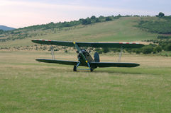 Old-fashioned biplane landed. Vintage camouflage biplane secured to the ground at a grassy airfield Stock Photo