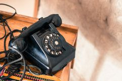 Old fashioned black telephone in retro/vintage style from long gone era. Old fashioned black telephone in retro/vintage style on the wooden table, from long gone royalty free stock photo