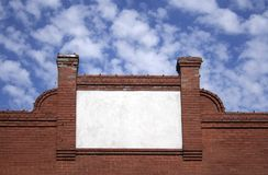 Old-Fashioned Blank Sign. Blank sign on old brick building, background of blue sky/white clouds Stock Photos