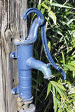 Old fashioned blue cast iron water pump with handle for pumping Royalty Free Stock Image