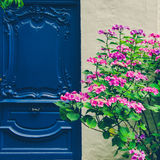 Old fashioned blue door with colorful flowers Stock Images