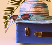 Old fashioned blue suitcase for travel and beach hat Stock Photos