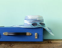 Old fashioned blue suitcase for travel and beach hat Royalty Free Stock Images