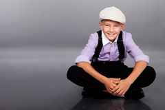Old fashioned boy sitting on gray background Royalty Free Stock Photos