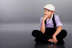 Old fashioned boy sitting on gray background Royalty Free Stock Photography