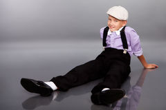 Old fashioned boy sitting on gray background Stock Photography