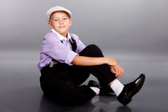 Old fashioned boy sitting on gray background Stock Photo