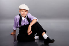 Old fashioned boy sitting on gray background Stock Photos