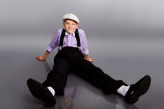 Old fashioned boy sitting on gray background Royalty Free Stock Image