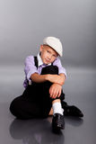 Old fashioned boy sitting on gray background Royalty Free Stock Photo