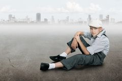 Old fashioned boy sitting on a ground near city Royalty Free Stock Image