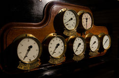 Old fashioned brass dials on wood  instrument panel Stock Photo