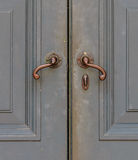 Old-Fashioned Bronze Handles of Gray Door. Old-Fashioned Bronze Handles of Old Gray Door royalty free stock photos