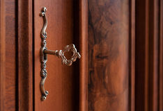 Old-fashioned bronze key. In a keyhole of a wooden door stock image