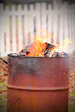 Old Fashioned Burn Barrel. Flames and heat waves while burning garbage in an old fashioned steel burn barrel. Shallow depth of field with picket fence in stock images