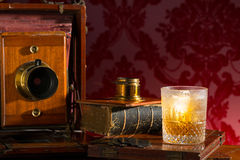 Old fashioned camera still life with whiskey Royalty Free Stock Images