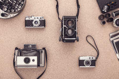 Old fashioned cameras on wooden cork table in te darkroom. View from above Stock Image