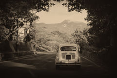 Old fashioned car. Sepia photo of a retro car going to mountains royalty free stock photography