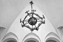 Old fashioned chandelier. Black painted old fashioned chandelier in a gothic building Royalty Free Stock Photo