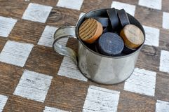 Old Fashioned Checker Game with Tin Cup. Old fashioned checker game with a tin cup full of checker pieces. The checkerboard is brown and white stock photo