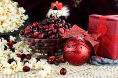 Old Fashioned Christmas. String of popcorn and cranberries with bowl of cranberries, popcorn, gift and ornaments in background. Shallow depth of field Royalty Free Stock Photos