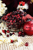 Old Fashioned Christmas. String of popcorn and cranberries with bowl of cranberries, popcorn, gift and ornaments in background. Shallow depth of field Stock Photo