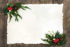 Old Fashioned Christmas Border. Old fashioned christmas background border with holly, mistletoe, ivy, juniper fir and pine cones on parchment paper over rustic Royalty Free Stock Photo