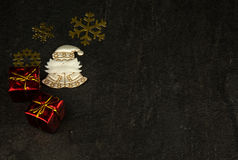 Old fashioned Christmas decoration. Christmas decoration with small packages,gold snowflakes and white Santa Claus on old, dark stone background.Flat,hotizontal Stock Images