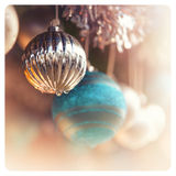 Old-fashioned Christmas decorations. Detail of christmas baubles with tinsel. Selective focus and bokeh background. Cross-processed with pastel shades, to create Royalty Free Stock Photo