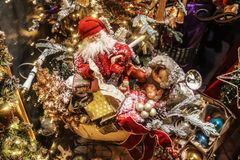 Old fashioned Christmas display with santa in his sled with presents and a doll and retro Christmas ornaments in front of a tree -. Blurred and bokeh royalty free stock images
