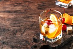 Old Fashioned - classic alcoholic cocktail with bourbon whiskey, bitter, cane sugar and ice in retro glasses on vintage bar. Counter, place for text royalty free stock image
