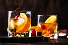 Old Fashioned - classic alcoholic cocktail with bourbon whiskey, bitter, cane sugar and ice in retro glasses on vintage bar. Counter, place for text stock photography