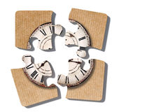 Old-fashioned clock print on puzzle pieces. 3d rendering of close-up of four puzzle pieces with print of old-fashioned shabby clock on paper background Royalty Free Stock Images