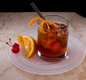Old fashioned cocktail. Served on a plate with orange and cherries Royalty Free Stock Photo
