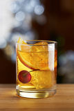 Old fashioned cocktail with a cherry. On fancy background Royalty Free Stock Images