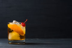 Old fashioned cocktail. With cherry and orange peel Stock Photo