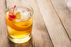 Old fashioned cocktail. With cherry and orange peel Royalty Free Stock Photos
