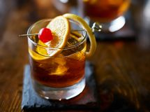 Old fashioned cocktail garnished with cherry, orange and lemon peel. Shot with selective focus stock image