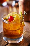 Old fashioned cocktail garnished with cherry, orange and lemon peel. Shot with selective focus royalty free stock photography