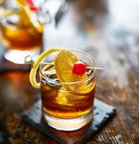 Old fashioned cocktail garnished with cherry, orange and lemon peel. Shot with selective focus royalty free stock photos