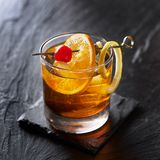 Old fashioned cocktail garnished with cherry, orange and lemon peel. Shot with selective focus royalty free stock photo