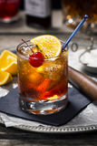 Old Fashioned Cocktail with Ingredients. An Old Fashioned cocktail in a vintage bar setting with the ingredients and tools in the background. Old Fashioneds Stock Image