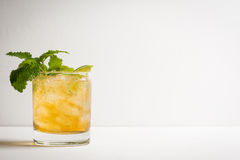 Old fashioned cocktail with lime and mint. On the wooden table Stock Images